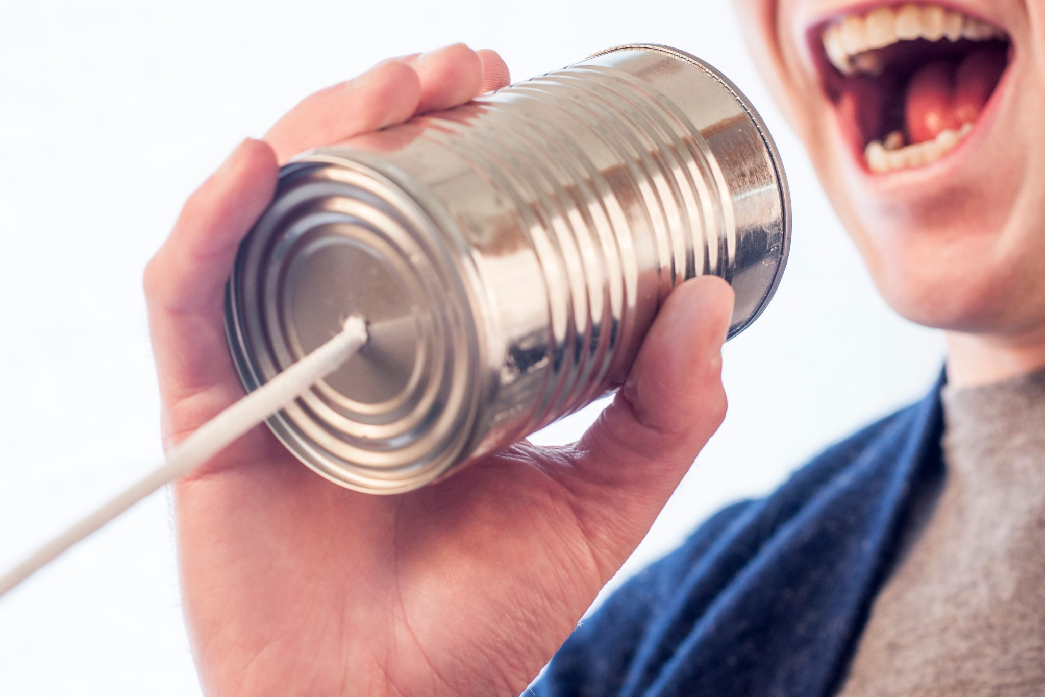 A person with a tin can and string showing that trying to contact hmrc takes so long