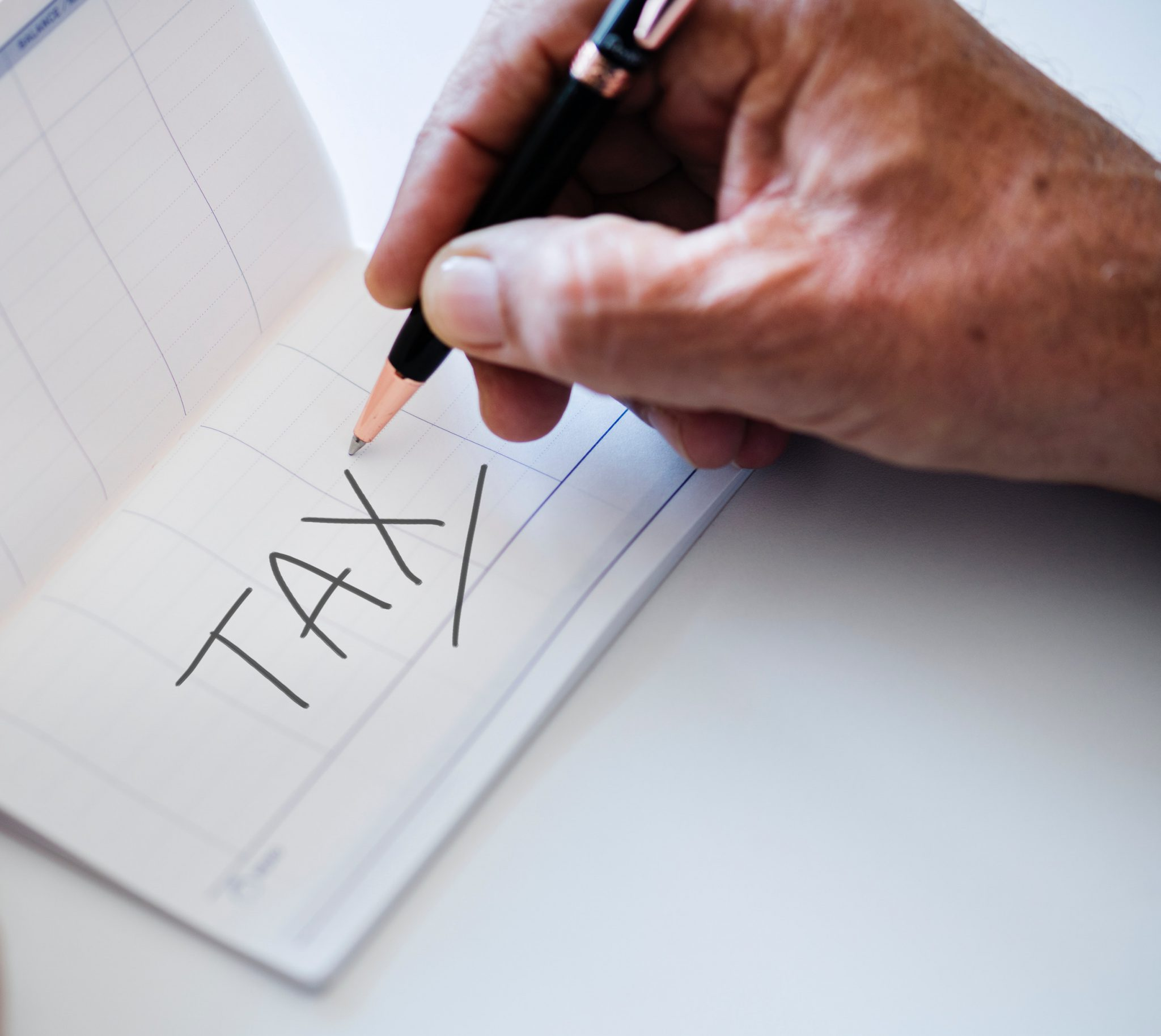 A piece of paper with the word tax written on it reminding you to have your Self-Assessment tax return in on time or you will be fined